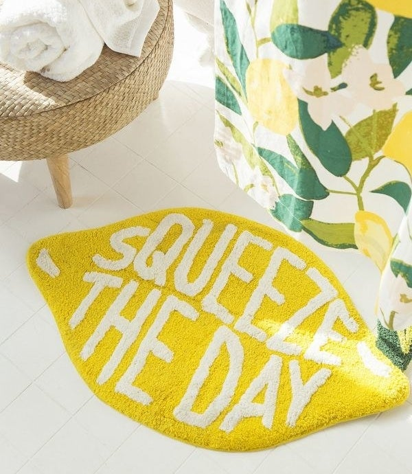 Lemon shaped bath mat that says Squeeze The Day