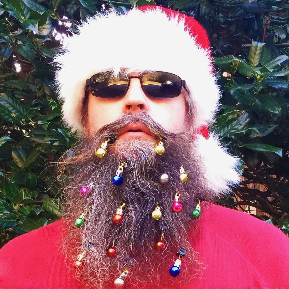 A person wearing tiny ornaments in their beard