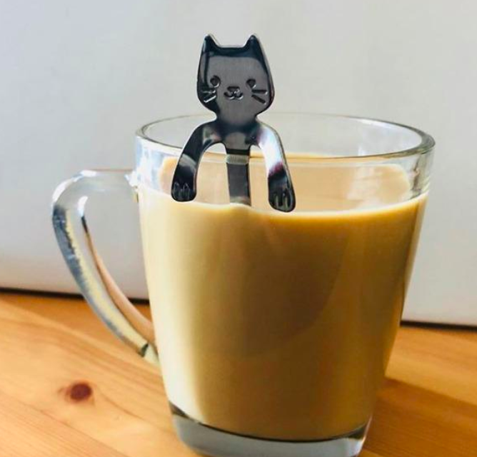 Cat-shaped spoon resting on the edge of a clear coffee cup