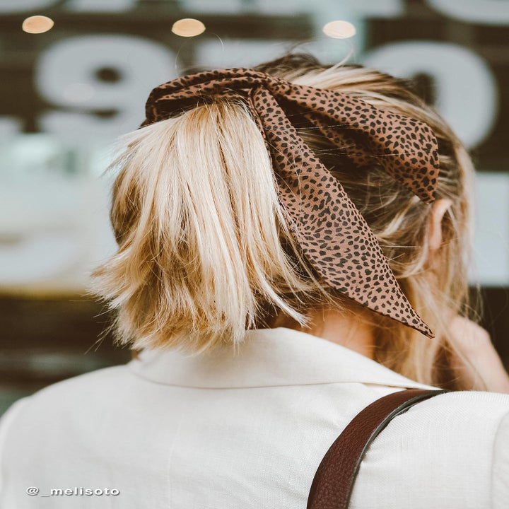 model wearing an animal print bow scrunchie in her hair
