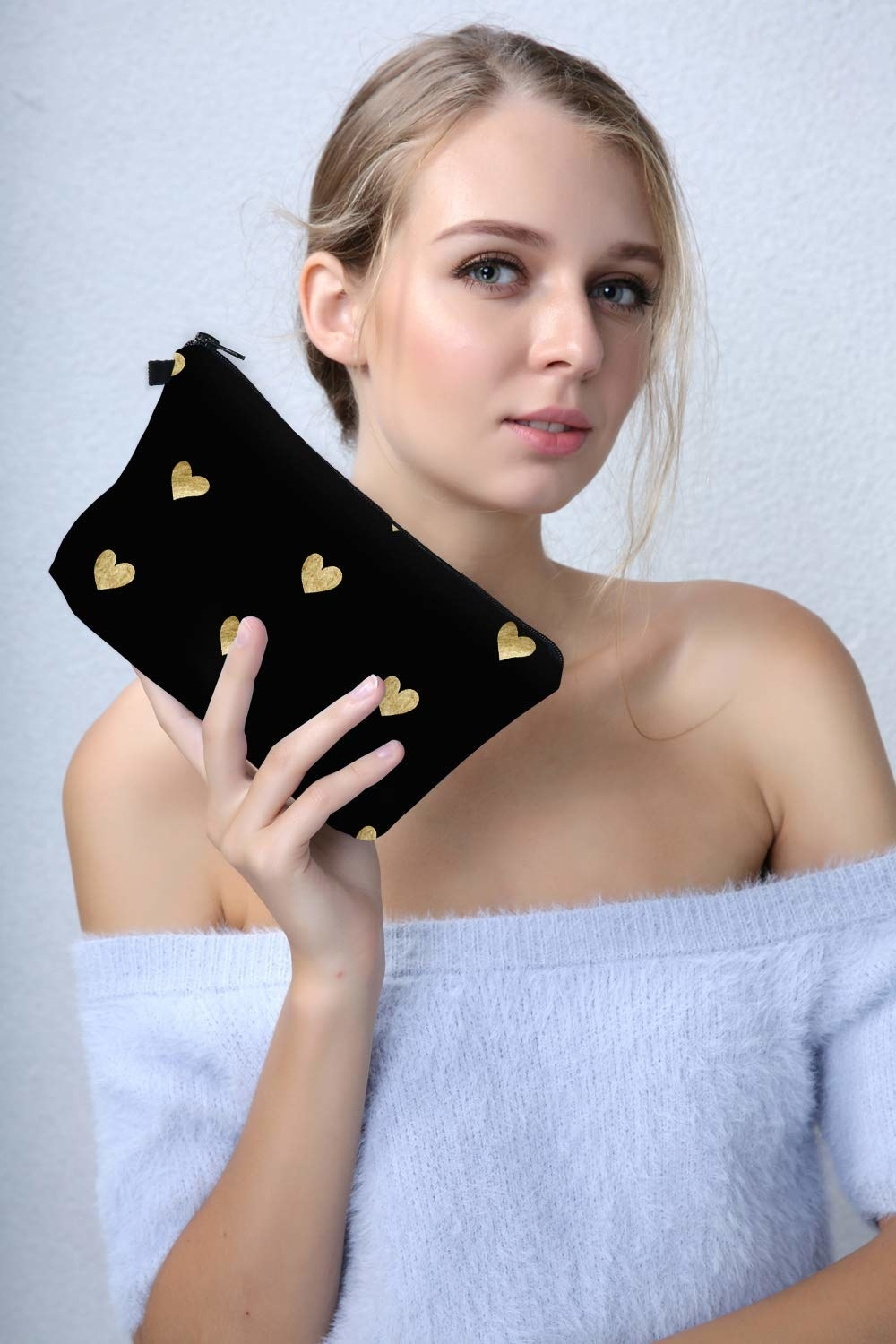 Model holding the black pouch with gold hearts