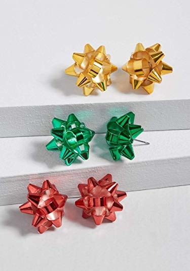 three pairs of stud earrings that look like Christmas wrapping bows