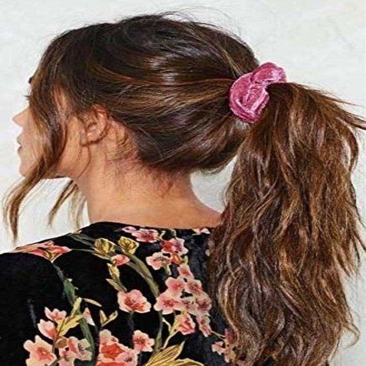 person wearing a pink velvet scrunchie with a pony tail