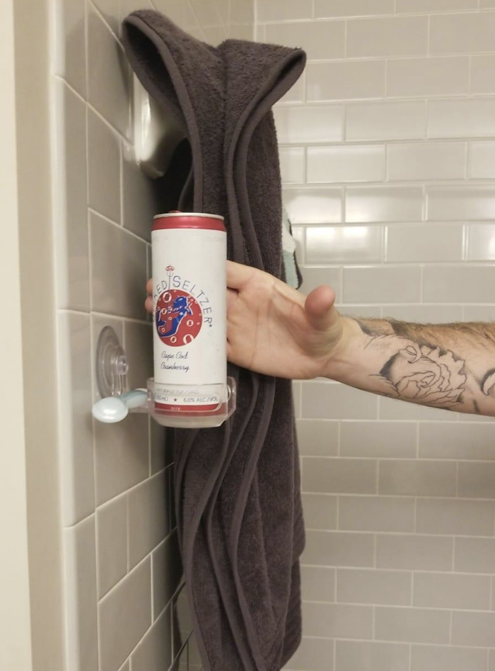 reviewer reaching for a can of alcoholic seltzer sitting on the cup holder