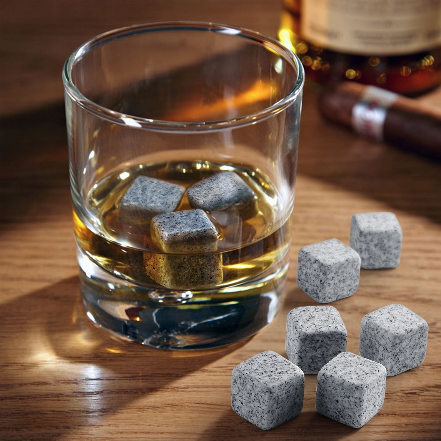 Several whiskey stones next to and inside a glass of whiskey