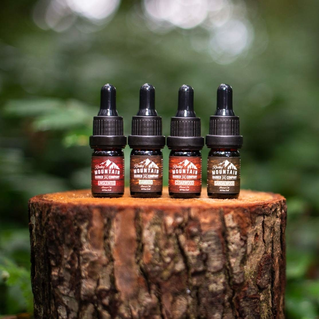 Four bottles of beard oil on a log
