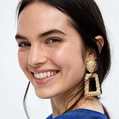 model wearing gold door knocker earrings