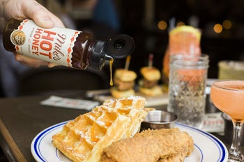 A person pouring the hot honey over a plate of chicken and waffles