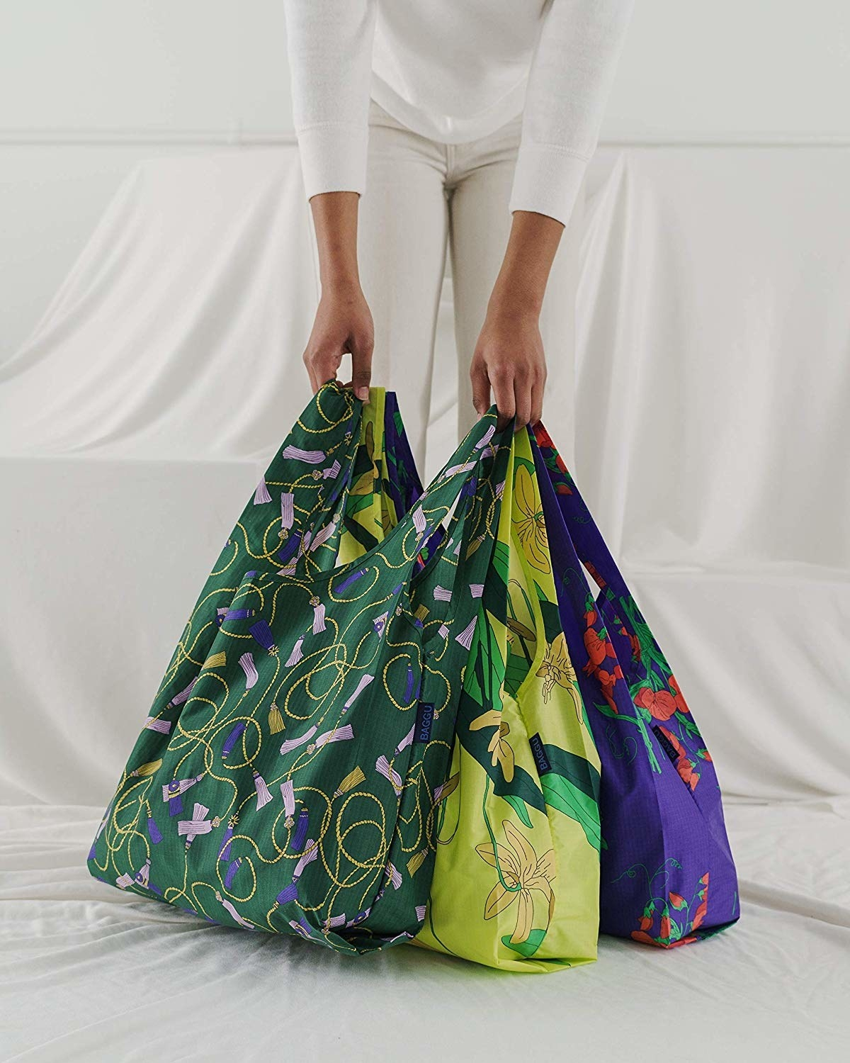 model holding three various patterned reusable totes