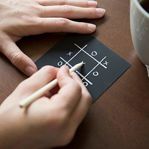 person placing tic-tac-toe on one of the notes