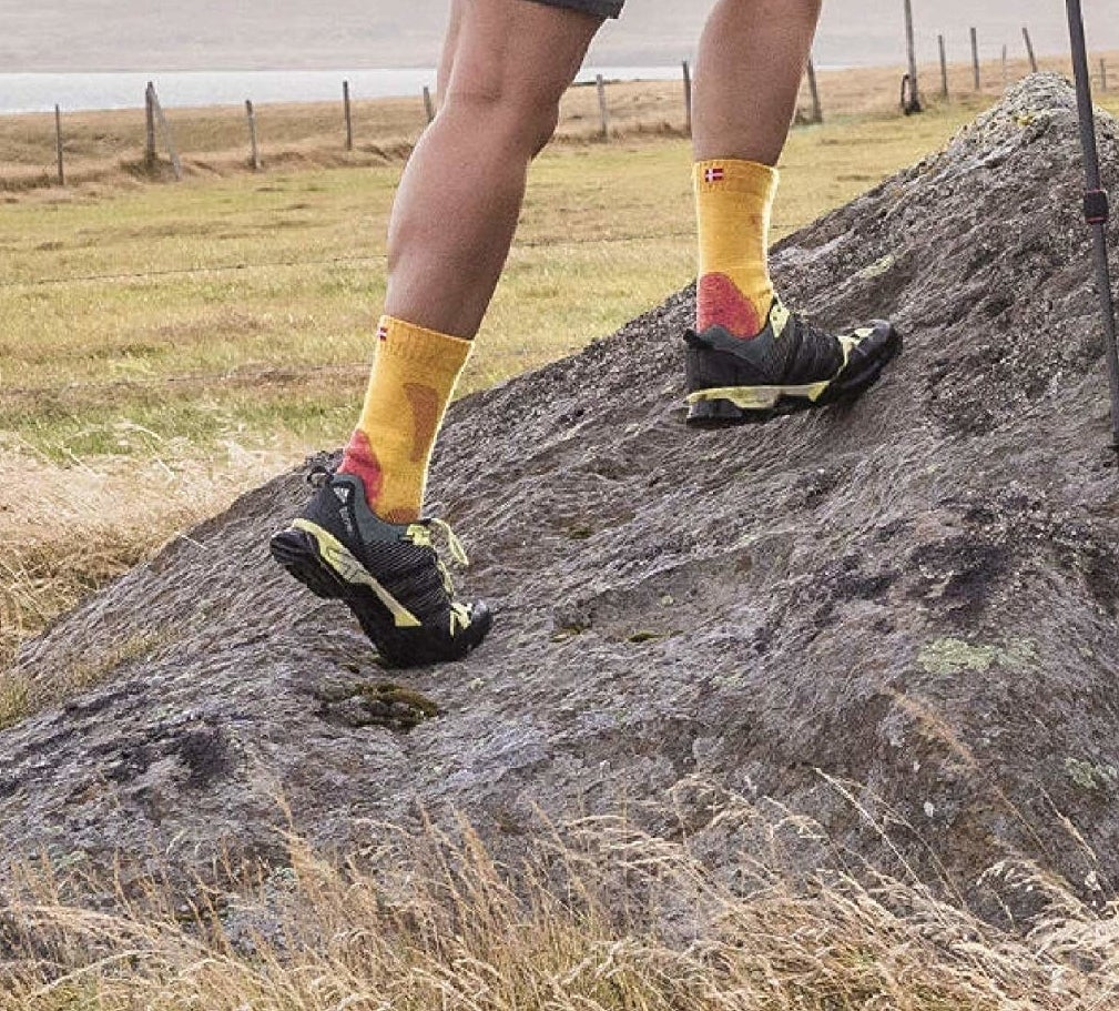 person wearing the socks and walking up a rock