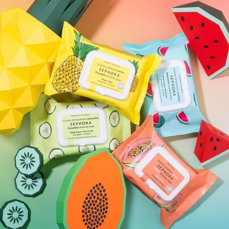 A variety of Sephora's makeup wipes stylized on a bright table with fake fruits