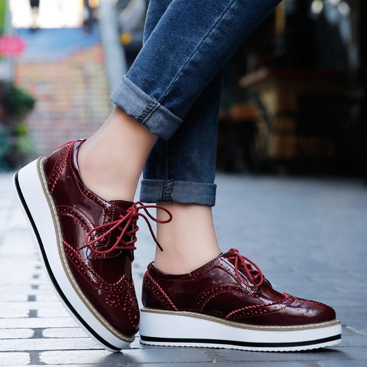 A model wearing the burgundy patent oxfords with chunky white and black platform soles
