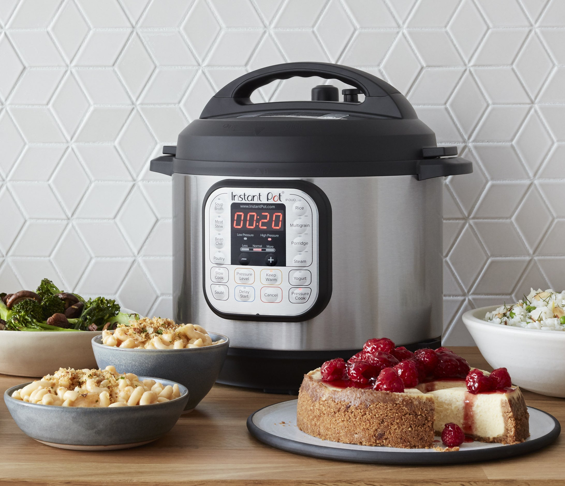 The instant pot on a kitchen table covered in plated food