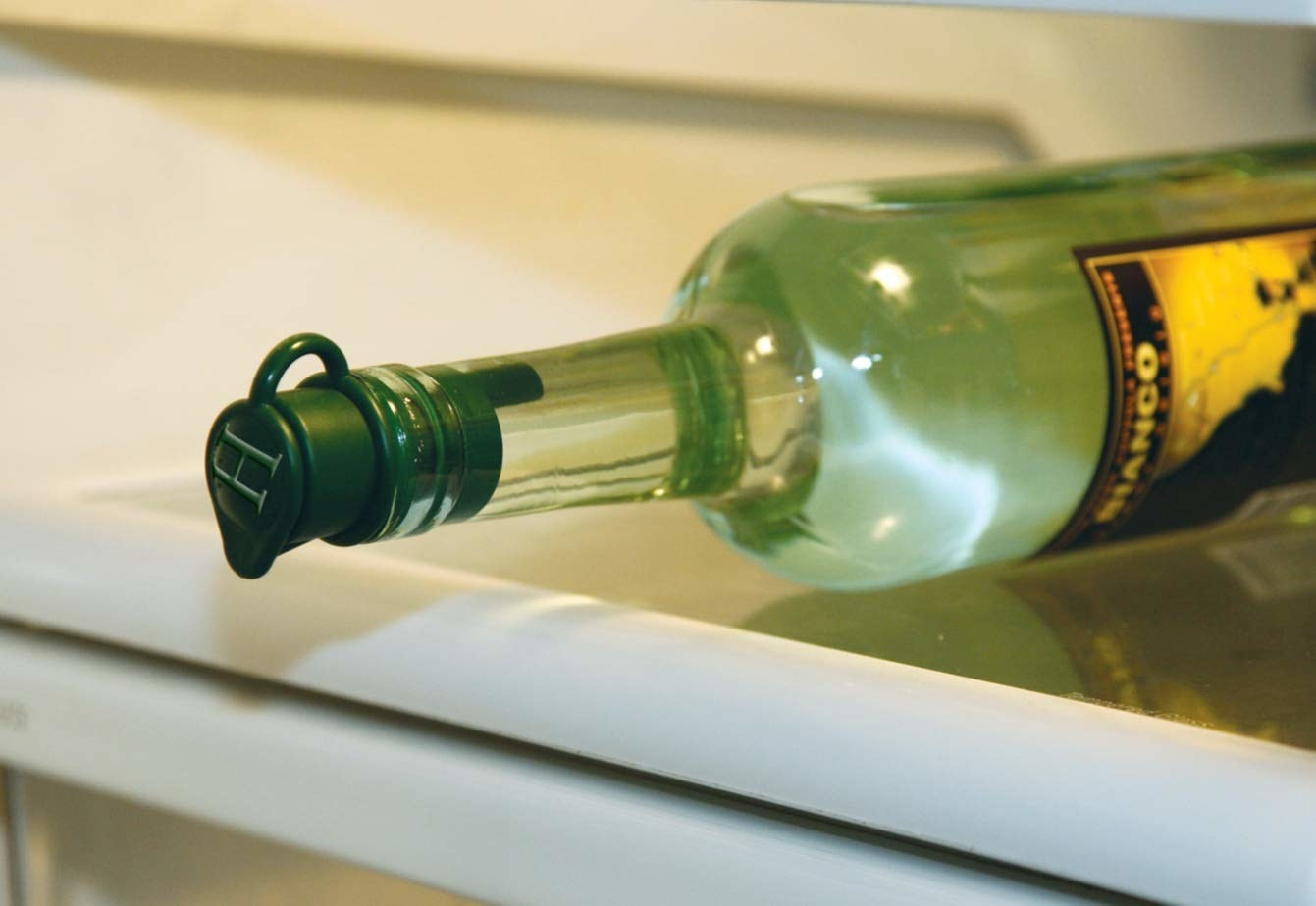 A bottle resting on its side on a fridge self with the stopper inside