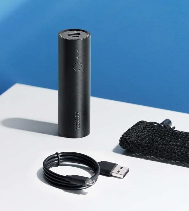 small black cylindrical charger with charging cord and mesh carrying bag
