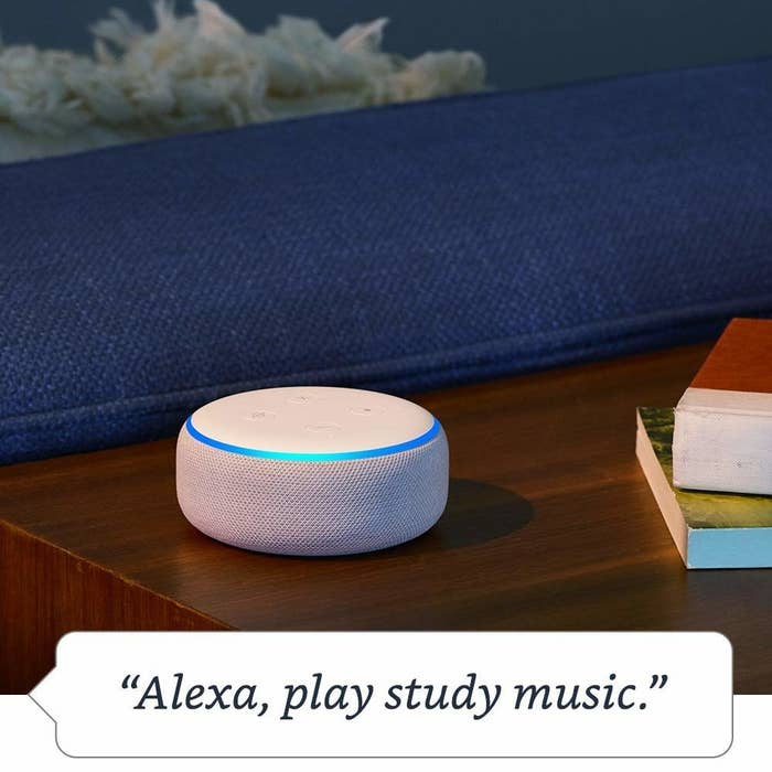 "A round white Echo Dot ringed with a blue light sits on a wooden table with the phrase ""Alexa, play study music."" in a speech bubble below it."