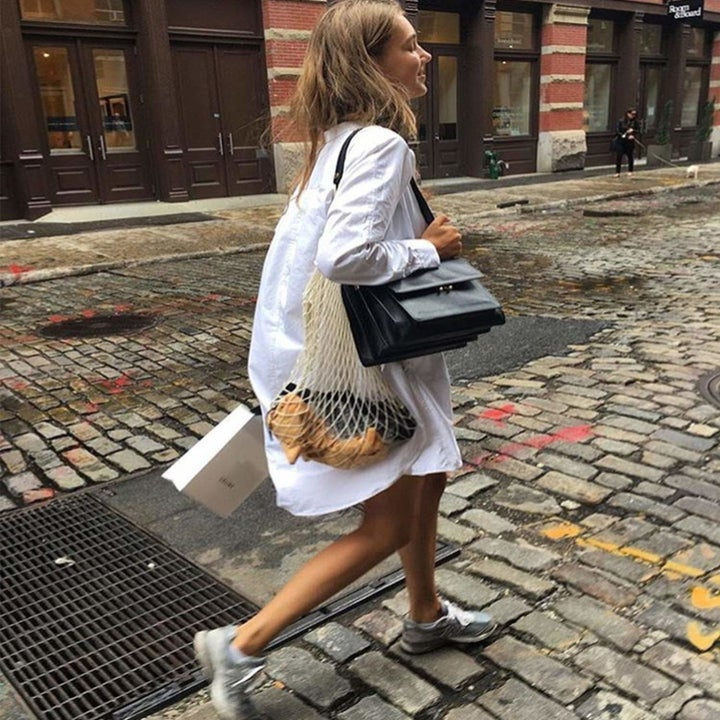 model walking on a street and carrying items in the bag