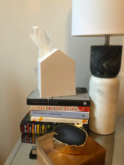nightstand with a stack of books and the square white house-shape tissue box on the stack