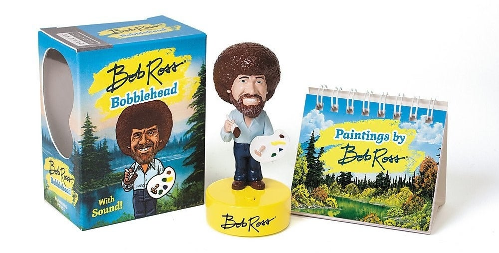 the Bob Ross bobble head with a book of paintings