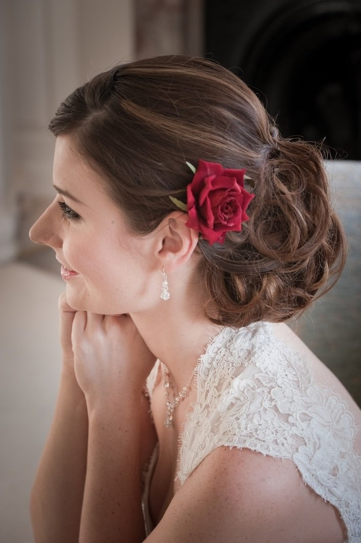A smiling person with a rose clip in their hair.