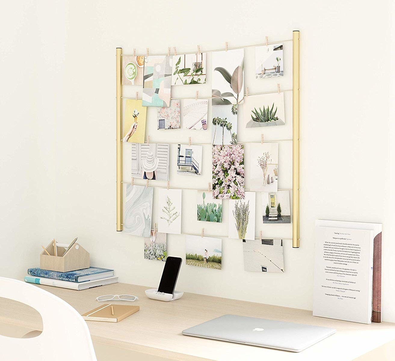 A clothespin photo display hanging above a desk