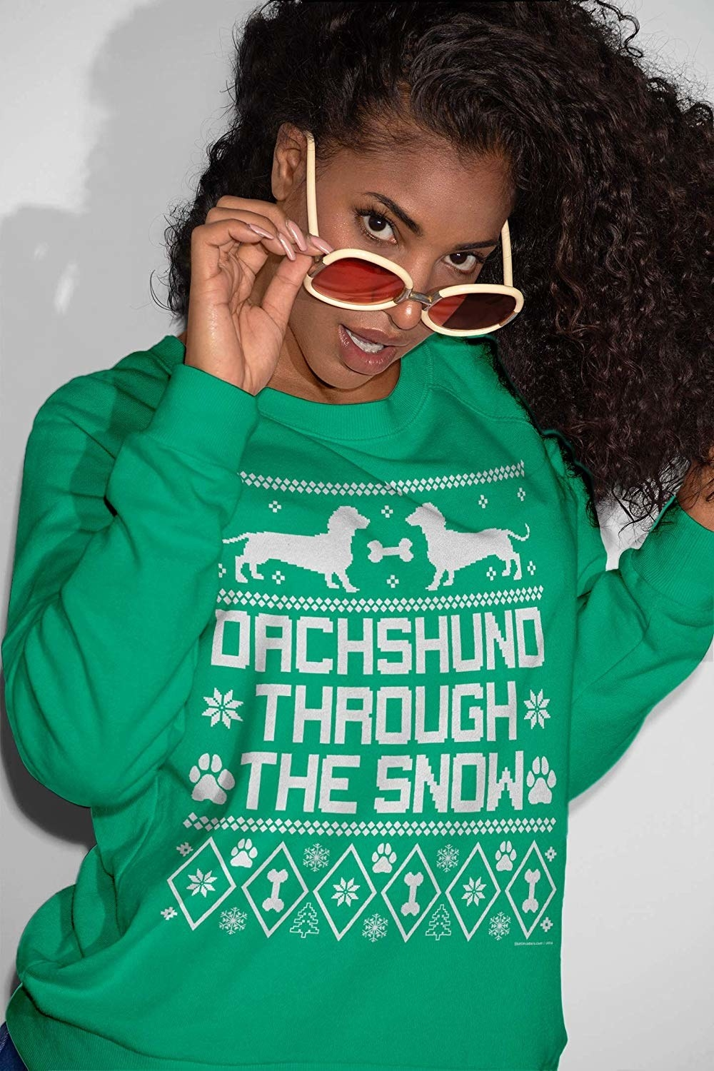 """A model in the green sweatshirt that says """"dachshund though the snow"""""""