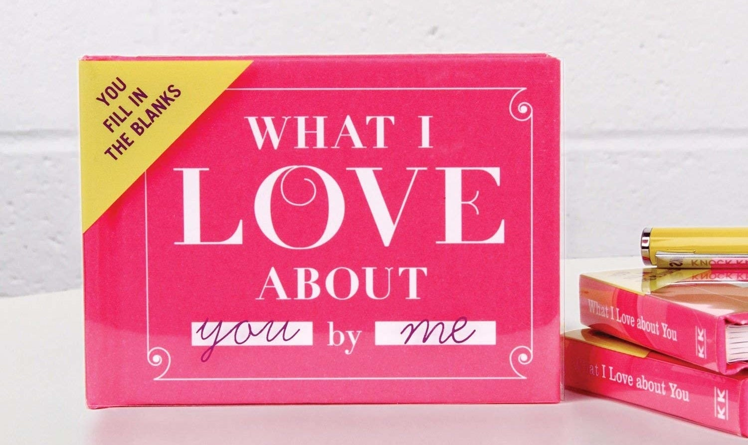 "Small pink book called ""What I Love About You by Me"" and the message ""You fill in the blanks"" in the upper-left corner."