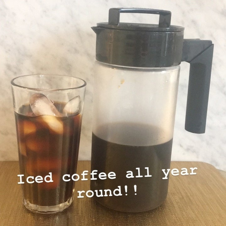 """iced coffee in clear glass next to the cold brew maker labeled """"iced coffee all year round"""""""