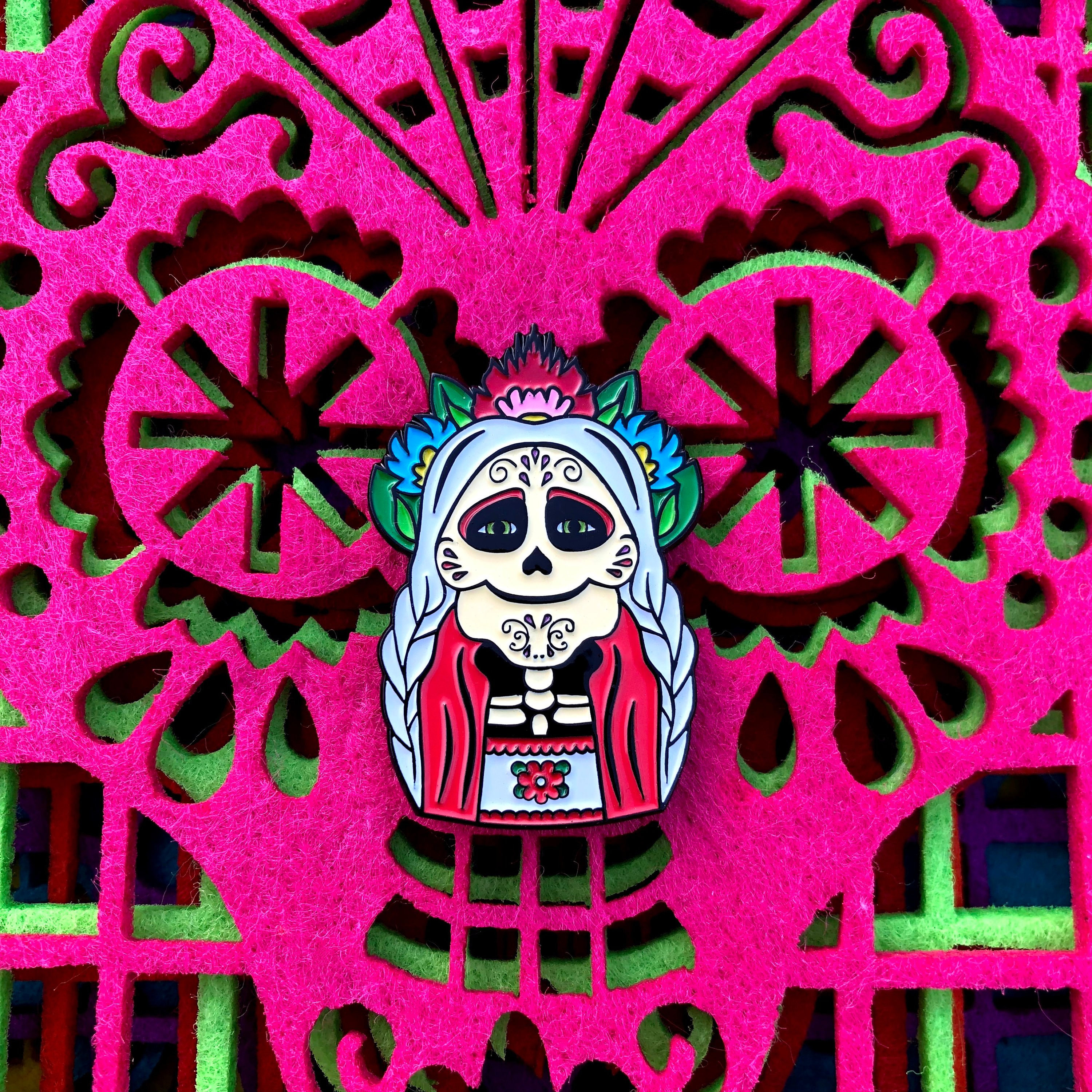 the enamel pin of mama coco as a skeleton