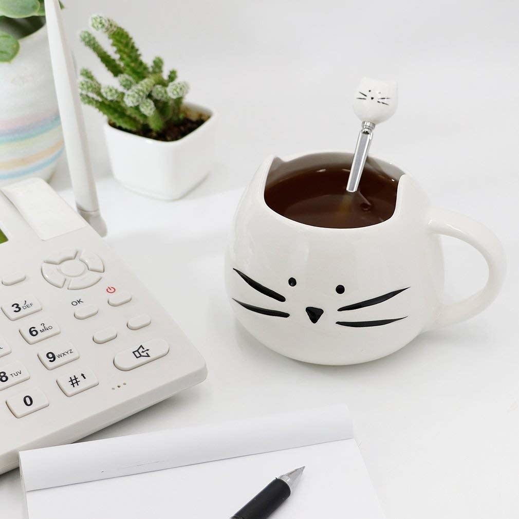 A coffee mug with a cat face on it