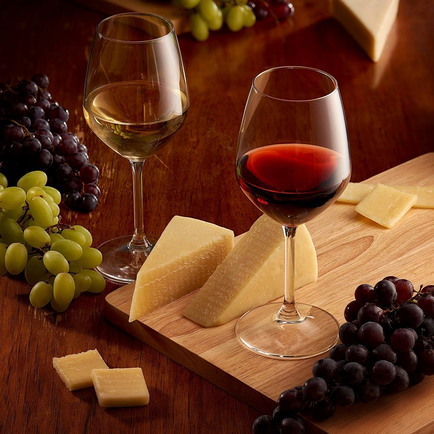 Two glasses of wine next to a board of cheese and grapes