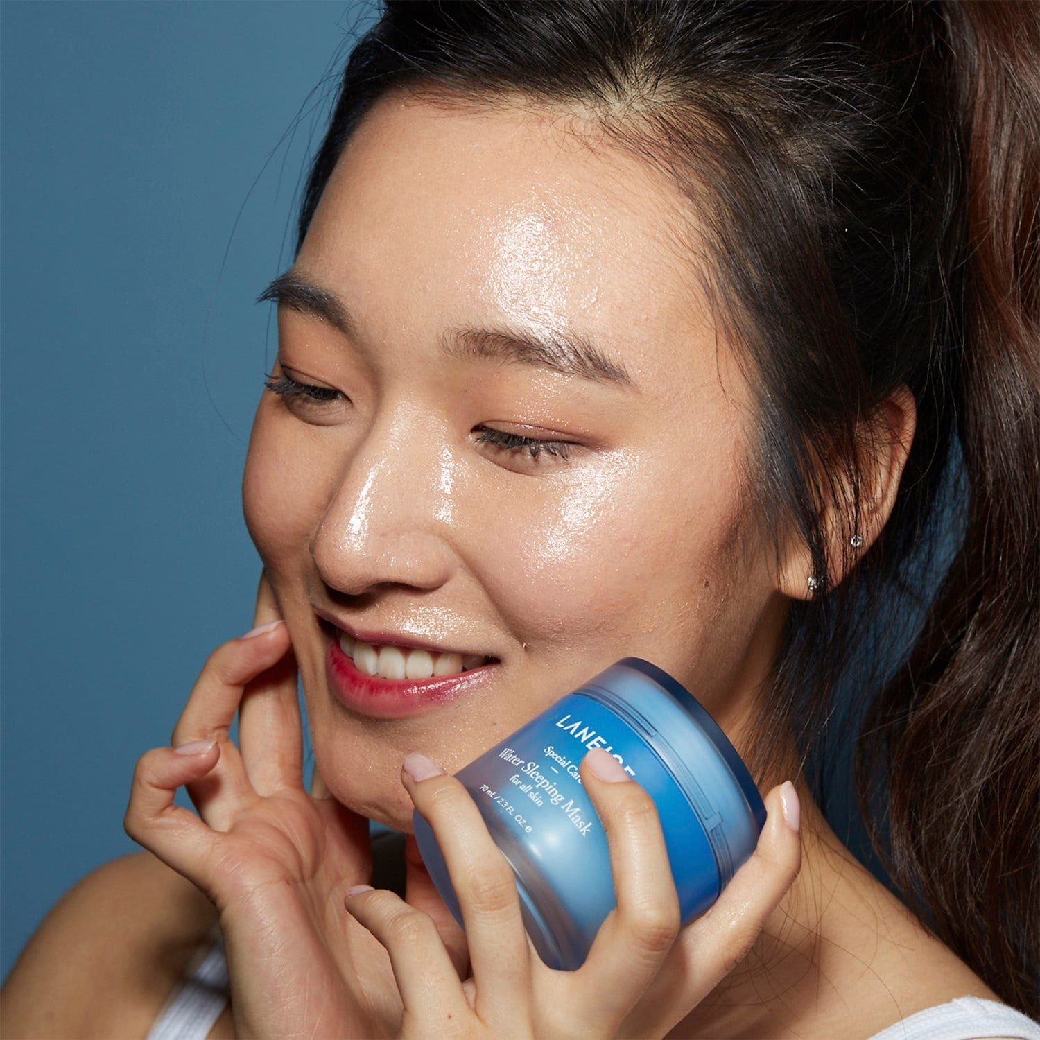 A model with glowing skin holding the jar of mask