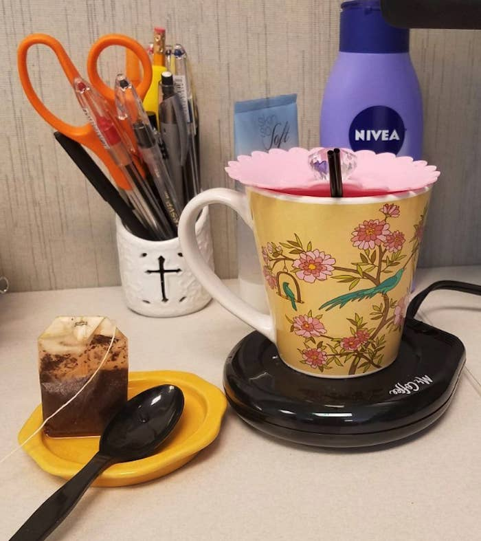 A mug sitting on top of the Mr. Coffee mug warmer, which looks like a thick coaster.  There's also a spoon and a tea bag sitting on an actual coaster right beside it. This warmer is sitting on a desk.