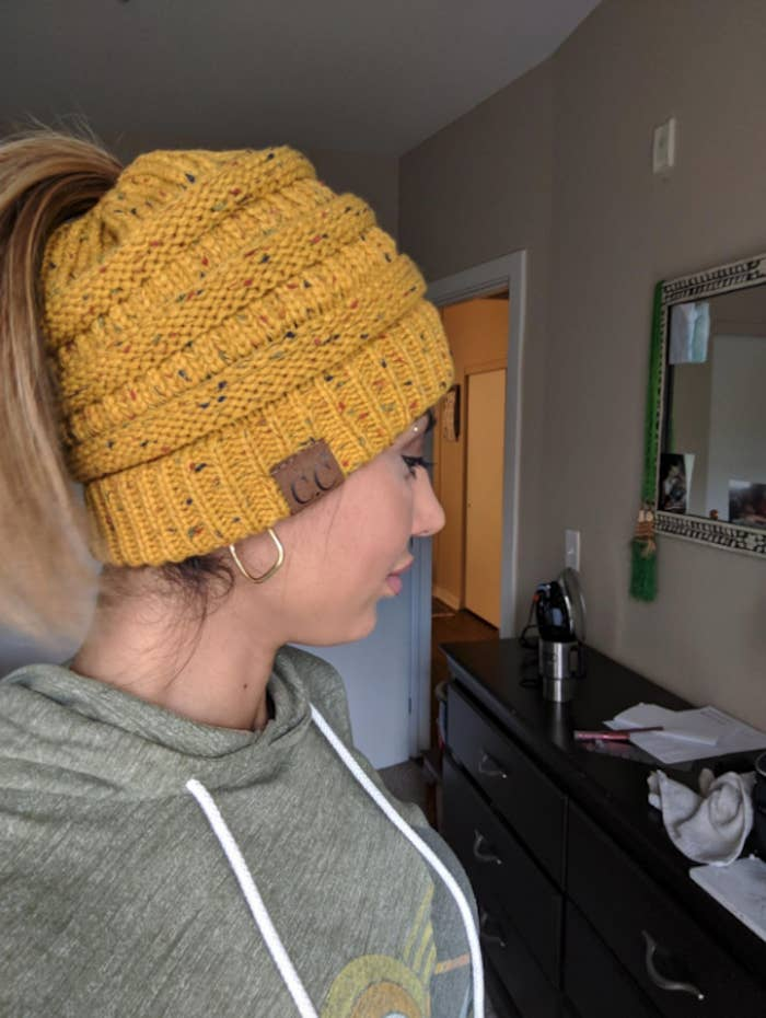 reviewer wearing a yellow knit beanie with her ponytail coming out of the hole at the top