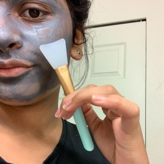 A reviewer applying a charcoal face mask with the brush