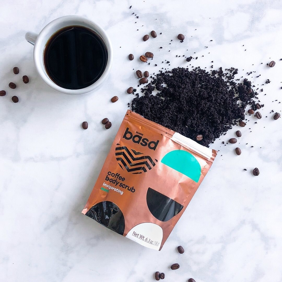 A bag of coffee body scrub lying half open on a table with coffee beans mixed in
