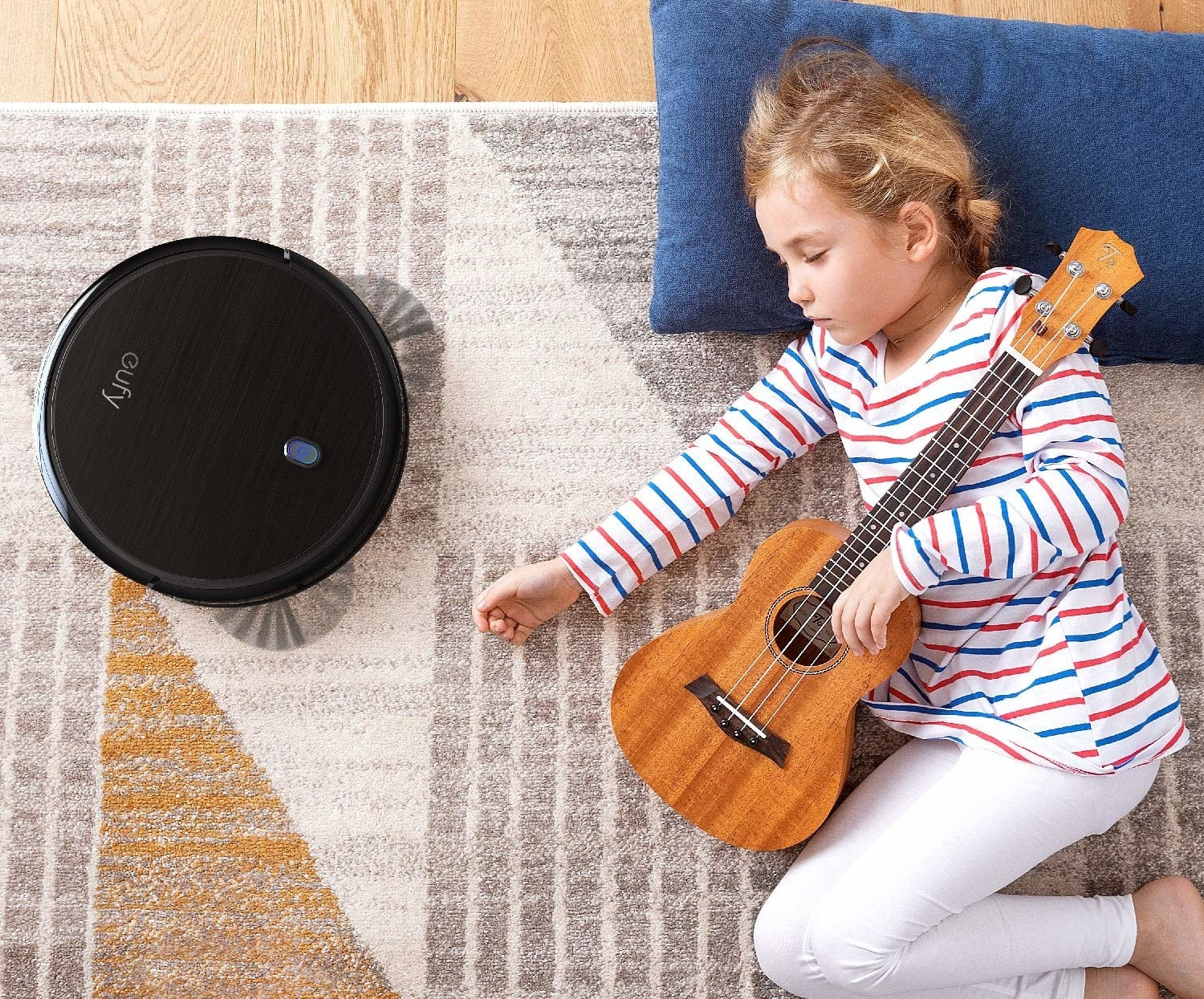 A child lying on the floor with a robot vacuum cleaning the rug beside them