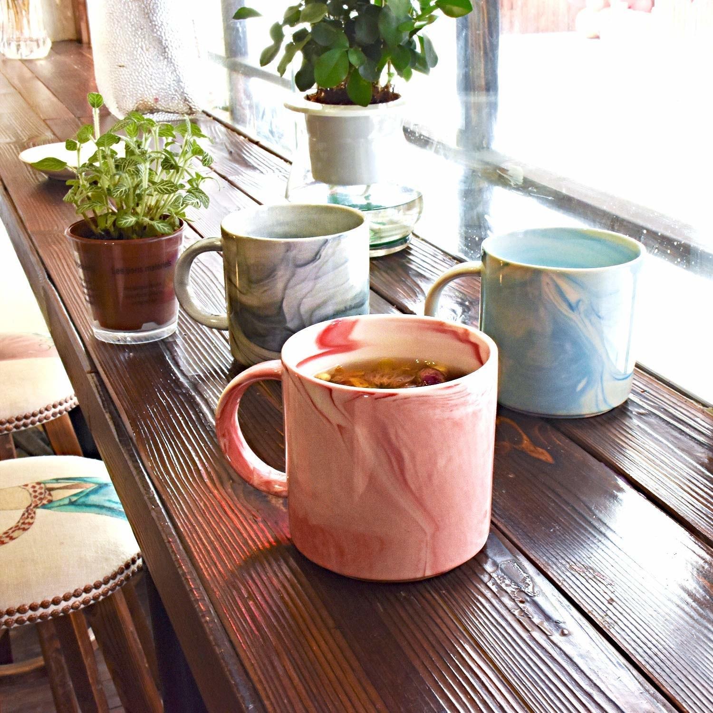 a pink marbled mug in front of a blue marbled mug and a grey marbled mug