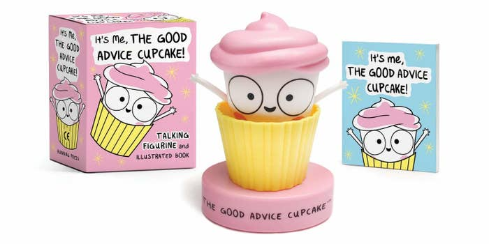 A plastic cupcake popping out of a muffin liner The cupcake has a face and two arms thrown into the air