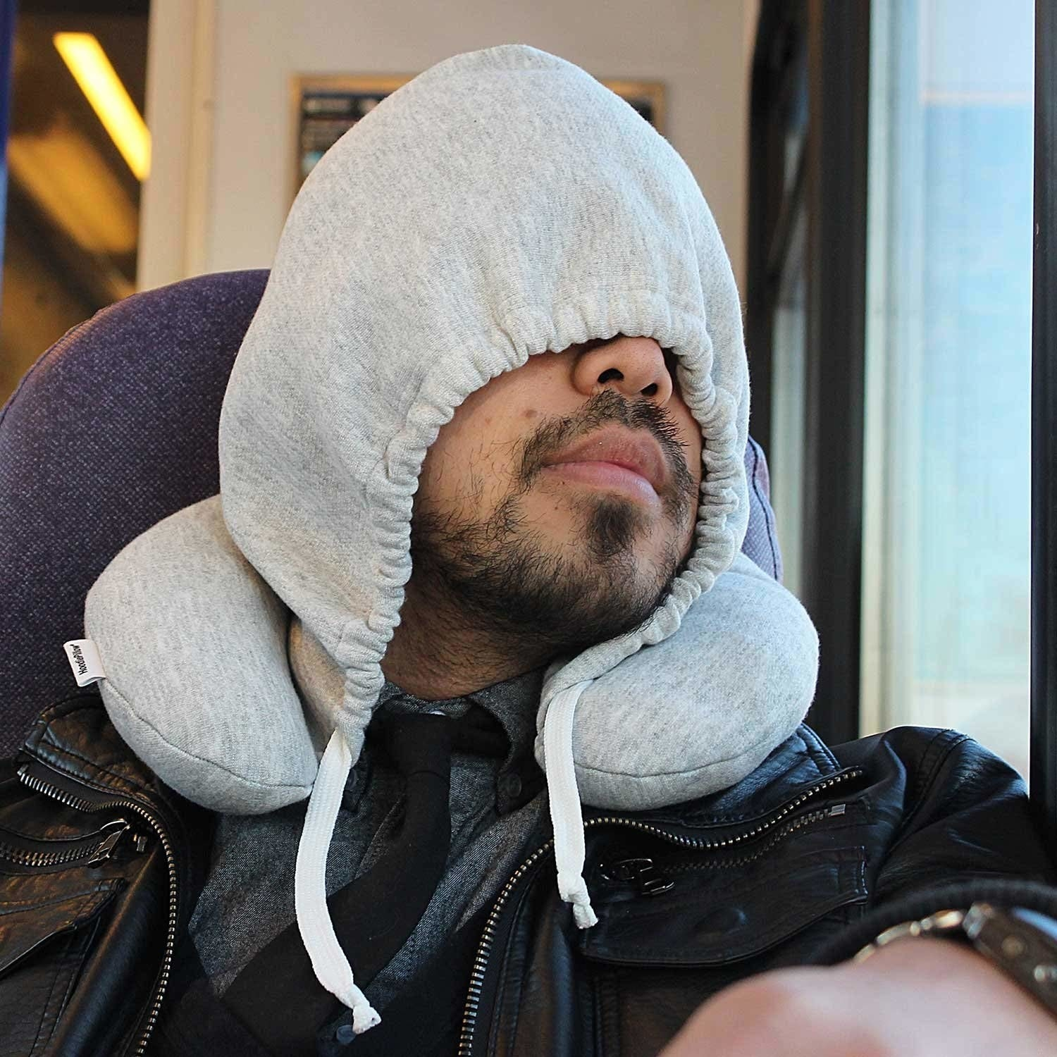 Person sleeping on train with pillow around neck and connected hood over eyes