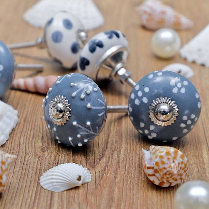 A close-up of the hand-painted globular knobs next to some seashells