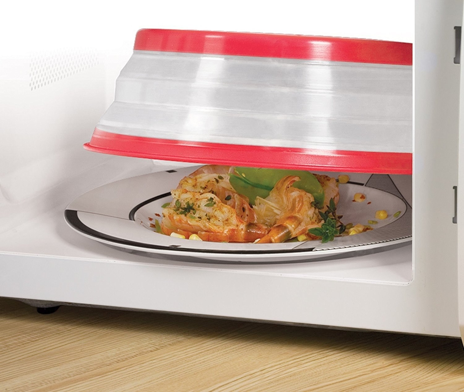 The plastic splatter guard with a red rim on top of a plate of leftovers in a microwave