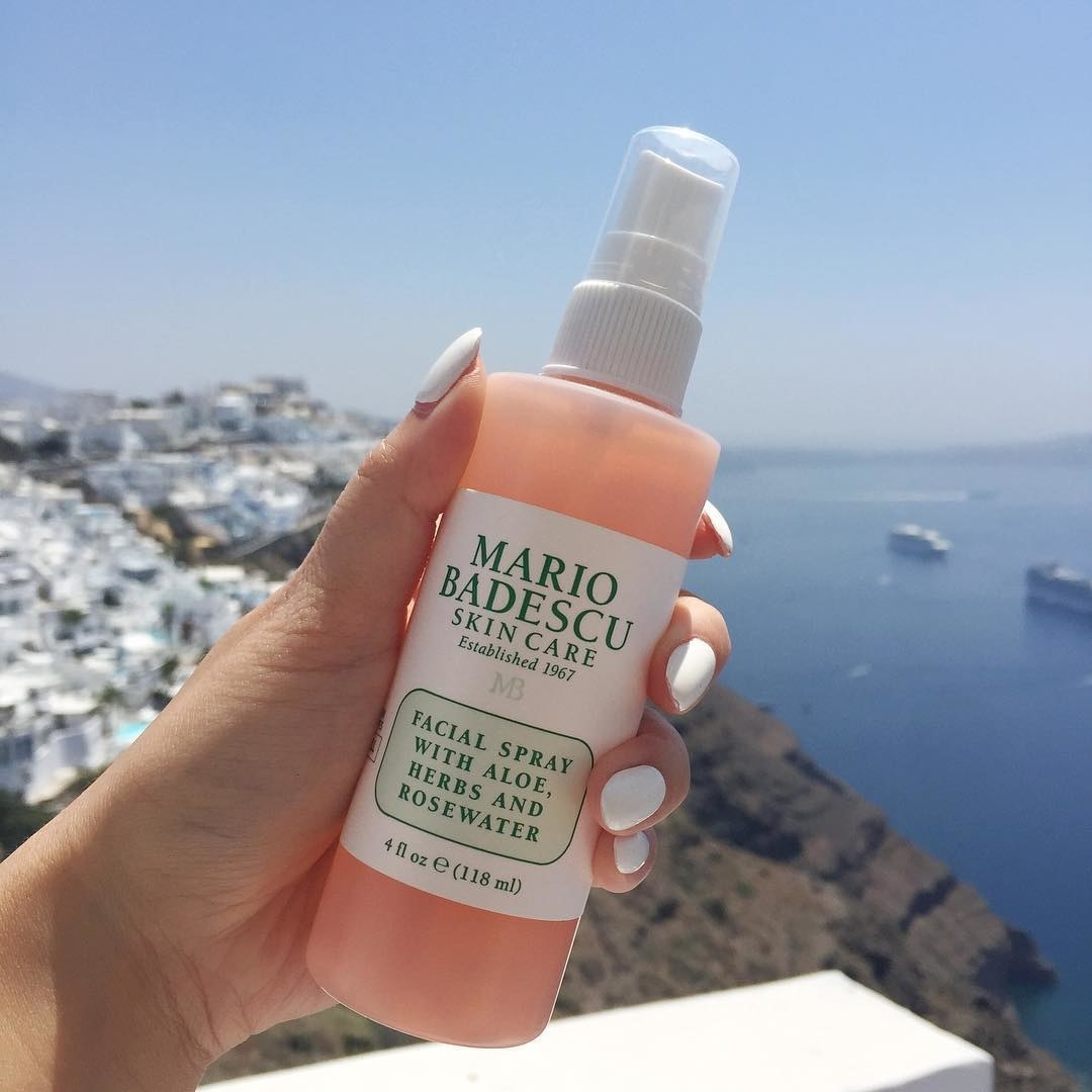 hand holding the bottle with a scenic Greek background
