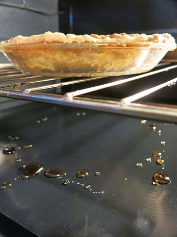 The oven liners catching drippings from a pie
