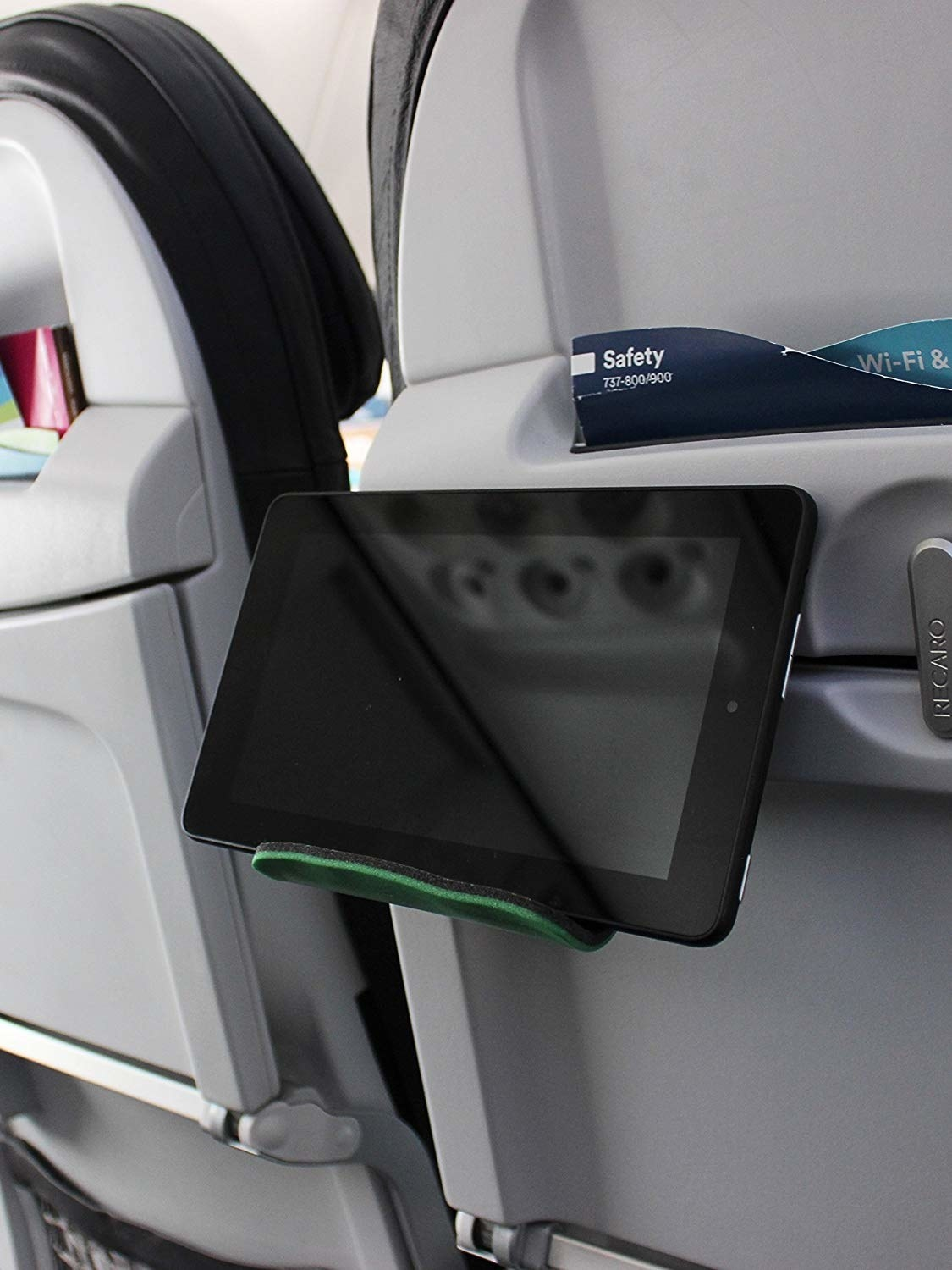 A tablet held up on a seat tray table