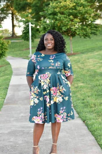 reviewer wearing the dress in green with pink and yellow flowers