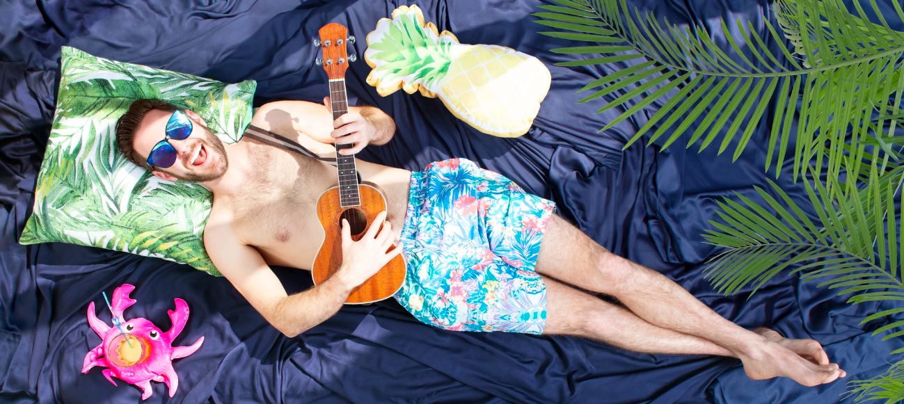 Person in boxers playing ukulele while laying on sheets
