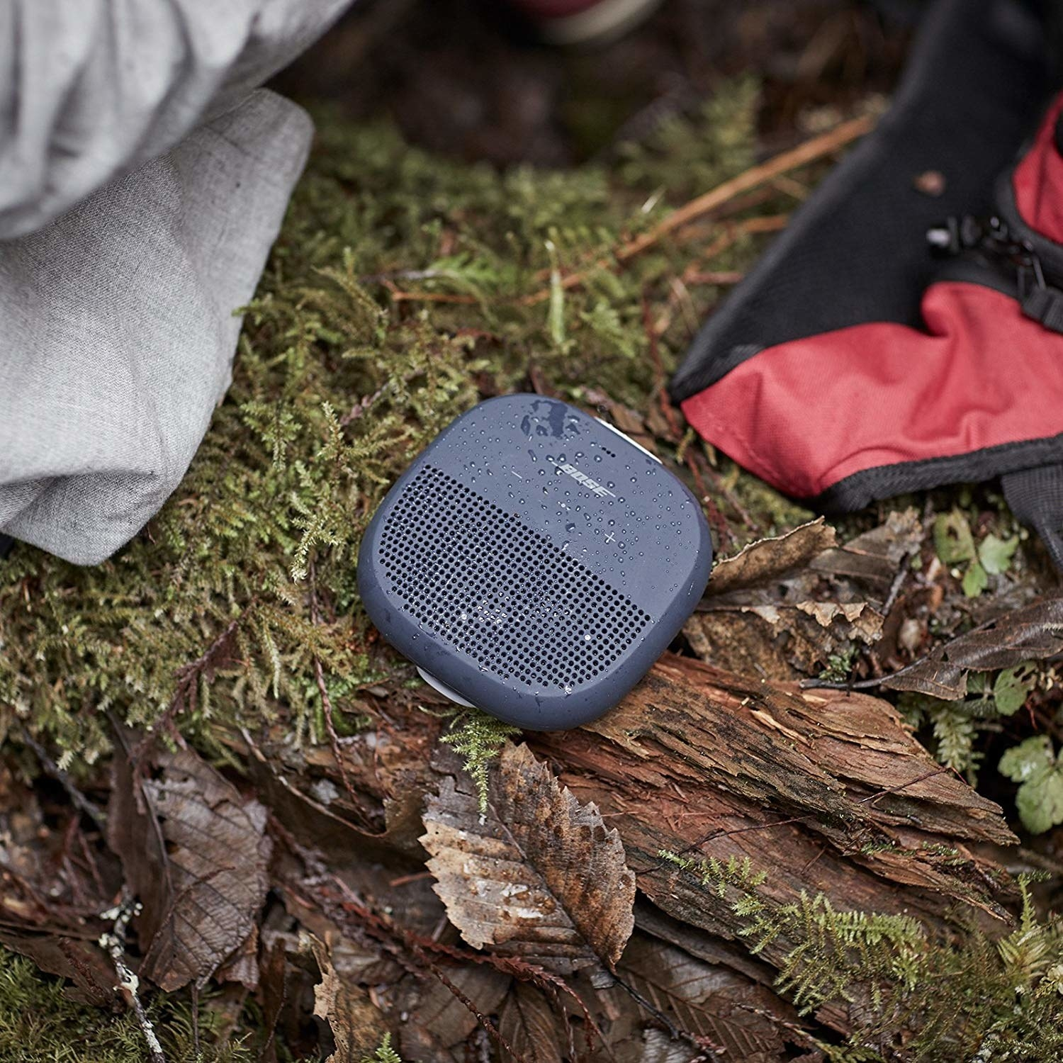 A Bose speaker on a mossy tree surrounded by camping gear
