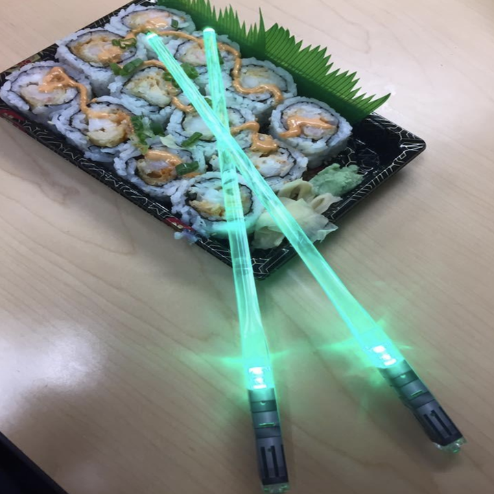 a pair of the green chopsticks with sushi rolls